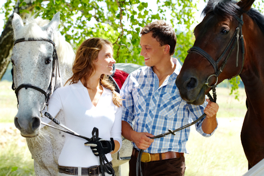 Happy couple with horses © 2010 by shirinosov iStockphoto