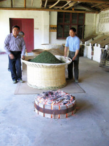 Hand drying high-end tea leaves in baskets